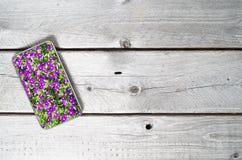 Dispositivo móvil moderno que muestra las flores violetas Imágenes de archivo libres de regalías