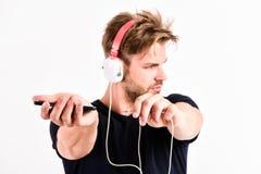Dispositivos acessórios musicais O homem escuta fones de ouvido e smartphone em linha da música Aplica??o da m?sica Tecnologia mo fotos de stock