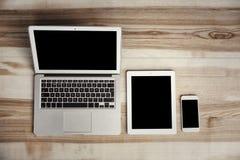 Dispositivos con las pantallas en blanco en fondo de madera imágenes de archivo libres de regalías
