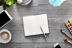 Dispositivos criativos do caderno da tabela de trabalho do desenhista do estudante no fundo de madeira cinzento foto de stock