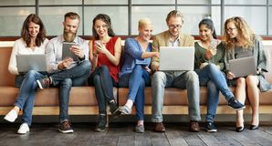 Dispositivos de Digitas da conexão dos povos da diversidade que consultam o conceito foto de stock royalty free