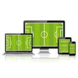 Dispositivos digitales modernos con el campo de fútbol en la pantalla Fotografía de archivo