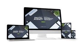 dispositivos do computador com Web site digital da agência na tela imagens de stock