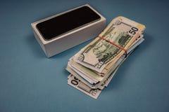 Dispositivos e d?lares do iPhone de Apple em um fundo monof?nico azul Voronezh, R?ssia - 3 de maio de 2019 fotos de stock royalty free