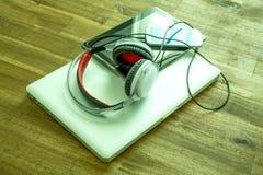 Dispositivos e fones de ouvido de Digitas em um Desktop de madeira Imagem de Stock