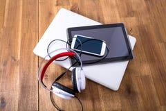 Dispositivos e fones de ouvido de Digitas em um Desktop de madeira Fotografia de Stock