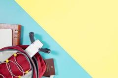 Dispositivos e objetos do curso do mochileiro na trouxa com objetos do vlogger do zangão e da câmera no rosa amarelo azul fotografia de stock