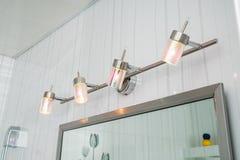 Dispositivos elétricos de iluminação no banheiro sobre um espelho foto de stock