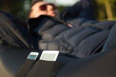 Dispositivos en un bolsillo inflable del sofá Imagenes de archivo
