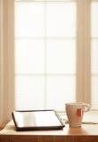 Dispositivos modernos de Digitas na tabela de madeira, backgrou borrado das janelas Imagem de Stock