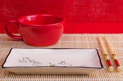 Dispositivos para el sushi en un fondo rojo Imagen de archivo