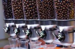 Dispositivos que publican los pequeños dulces redondos en chocolate fotos de archivo
