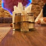Dispositivos que se colocan en la tabla en el restaurante: coctelera de sal, coctelera de la pimienta y soporte para las serville foto de archivo libre de regalías