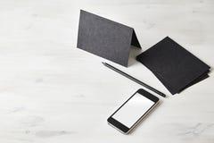 Disposizione in bianco della cancelleria Cartolina nera, matita, telefono cellulare sulla tavola di legno Fotografia Stock