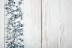 Disposizione con i dadi e le viti distribuiti sul lato destro del banco da lavoro di legno di DIY Fotografie Stock