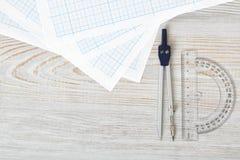 Disposizione con la bussola, il goniometro e la carta millimetrata su superficie di legno nella vista superiore Immagine Stock