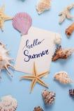 Disposizione creativa fatta delle conchiglie e della cartolina d'auguri variopinte differenti con ciao l'iscrizione di estate Fotografia Stock Libera da Diritti