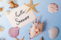 Disposizione creativa fatta delle conchiglie e della cartolina d'auguri variopinte differenti con ciao l'iscrizione di estate Fotografia Stock