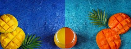 Disposizione creativa su un fondo del turchese e del blu con il mango, un vetro delle loro due metà di succo e le foglie di palma fotografia stock libera da diritti