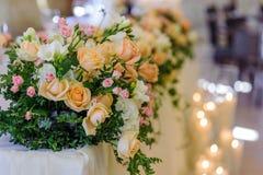 Disposizione dei fiori di nozze sui precedenti delle candele brucianti Immagine Stock
