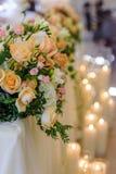 Disposizione dei fiori di nozze sui precedenti delle candele brucianti Fotografia Stock