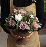 Disposizione dei fiori festiva delle rose di paleviolet e dei fiori del cotone nel fiorista del vaso che tiene al boutique dei fi fotografia stock libera da diritti