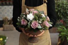 Disposizione dei fiori festiva delle rose di paleviolet e dei fiori del cotone nel fiorista del vaso che tiene al boutique dei fi immagine stock libera da diritti