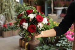 Disposizione dei fiori festiva delle rose rosse e dei fiori del cotone nel fiorista del vaso che tiene al boutique dei fiori immagine stock libera da diritti