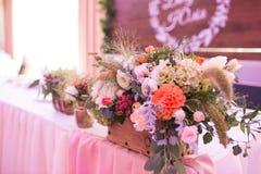 Disposizione dei fiori rustica in un vaso dorato ad un banchetto di nozze La Tabella ha impostato per un partito o un ricevimento fotografia stock libera da diritti