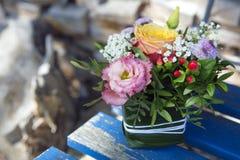 Disposizione dei fiori su una sedia di legno Fotografia Stock