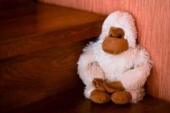 Disposizione dei posti a sedere bianca fatta a mano del giocattolo della scimmia sulle scale di legno marroni Fotografia Stock