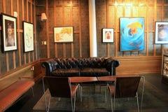Disposizione dei posti a sedere comoda nella sala, con materiale illustrativo che appende sulle pareti, su vecchi 77 hotel e sugl Fotografia Stock