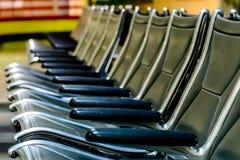 Disposizione dei posti a sedere vuota dell'aeroporto - sedie nere tipiche nell'attesa di imbarco Immagini Stock