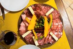 Disposizione dei tagli freddi delle specialità gastronomiche con vino rosso e il finocchiona affumicato del prosciutto Immagini Stock Libere da Diritti