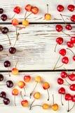 Disposizione delle ciliege mature su fondo di legno Fotografia Stock