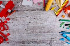 Disposizione delle matite, bottoni e clip, un aeroplano del giocattolo e frutti Su un fondo di legno con un posto per un'iscrizio immagine stock libera da diritti