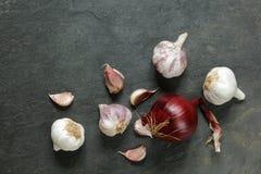 Disposizione di aglio e delle cipolle su una tavola naturale dell'ardesia Immagine Stock Libera da Diritti