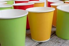 Disposizione di riciclaggio delle tazze di carta variopinte eliminabili, vetro di colore rosso, giallo e verde immagine stock