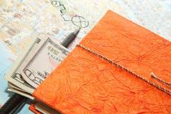 Disposizione di viaggio del primo piano del diario dei dollari, della mappa e del blocco note immagini stock libere da diritti