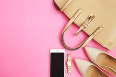Disposizione femminile del piano degli accessori La donna calza lo smartphone della borsa su fondo rosa Accessori beige della don Immagini Stock