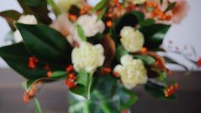 Disposizione floreale del primo piano Fiori in un vaso di vetro Donna che seleziona i fiori freschi per creare bello mazzo in vas stock footage
