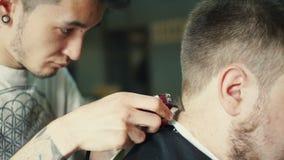 Disposizione perfetta Primo piano di retrovisione di giovane uomo barbuto che ottiene taglio di capelli dal parrucchiere con il r video d archivio
