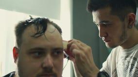 Disposizione perfetta Primo piano di retrovisione di giovane uomo barbuto che ottiene taglio di capelli dal parrucchiere con il r stock footage