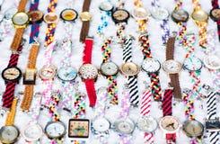 Disposizione piacevole di molti orologi variopinti su una superficie bianca fotografie stock
