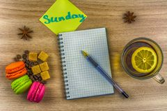Disposizione piana Autoadesivo con l'iscrizione domenica Tazza di tè con il limone Taccuino e penna, maccherone dei biscotti Chic Fotografia Stock Libera da Diritti