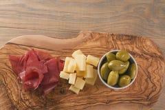 Disposizione piana con i antipasti italiani classici, breasola olive e parmigiano sul bordo verde oliva fotografia stock