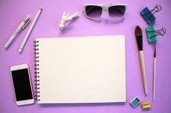 Disposizione piana con Libro Bianco e gli occhiali da sole su fondo viola Rifornimenti bianchi di arte e vista superiore dello sm Fotografia Stock Libera da Diritti