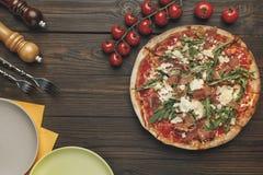 Disposizione piana con pizza italiana sistemata, pomodori andcherry della coltelleria fotografie stock