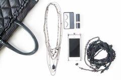 Disposizione piana degli accessori vuoti del taccuino, del cellulare e della donna dentro Fotografia Stock