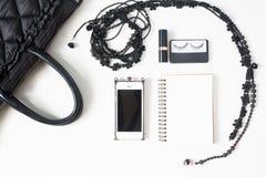 Disposizione piana degli accessori vuoti del taccuino, del cellulare e della donna dentro Immagini Stock